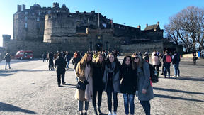 UMD LSBE student Courtney Cornelius in Scotland standing in front of a castle with other students.