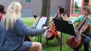 Betsy Husby, a music professor, with campers playing cellos outside