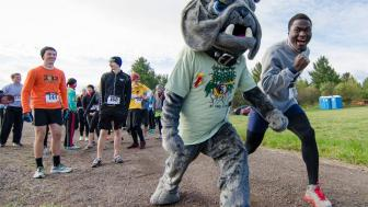Trail racers at UMD's Food and Farm Festival lineup with Champ