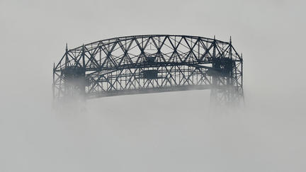 An aerial lift bridge partially obscured by fog.