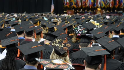"UMD students in caps and gowns. One cap is decorated with the words ""Go Dogs"""