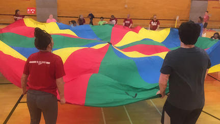 Adapted PE image - children holding the edges of a colorful parachute