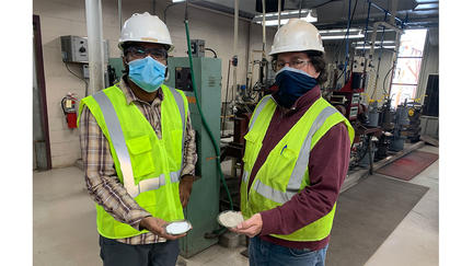 Two Natural Resources Research Institute scientists wearing masks hold alternative binders