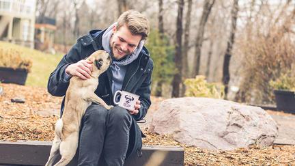 UMD student Benji Wedel with a pug dog.