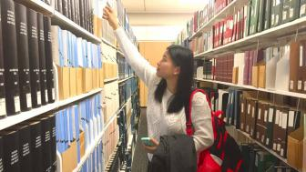 Brenda grabbing a textbook off of a shelf