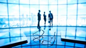 Generic business picture of glasses and blurry business people in the background
