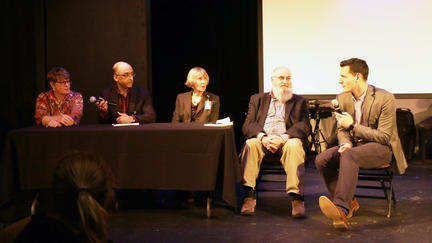 Two women and four men seated at a table for a panel discussion