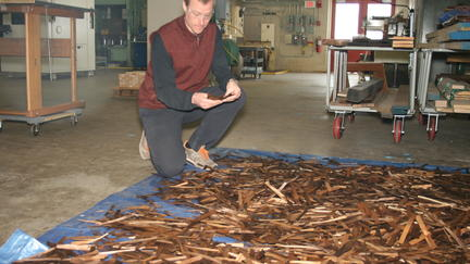 NRRI scientist Matt Aro inspects wood strands that were thermally modified in NRRI's pilot scale kiln.