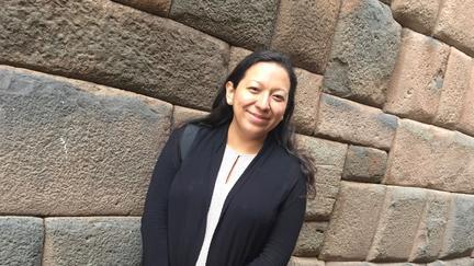 UMD Professor Jennifer Gómez Menjívar standing in front of stone wall