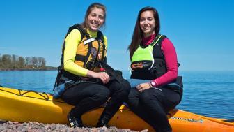 UMD alumna who paddled around Lake Superior sit by their kayaks on the shoreline