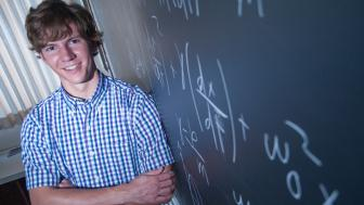 Mark Kallevig and a blackboard covered in formulas