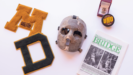 An image showing artifacts from UMD's history. Two patches, goalie mask, championship ring, hockey puck, and a Bridge magazine.