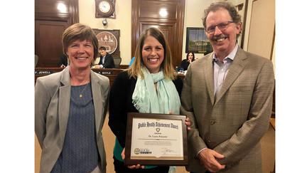 Dr. Laura Palombi (center) standing holding framed award, flanked by Amy Westbrook, director of Public Health on Laura's right, and Commissioner Frank Jewell, who chairs the Health and Human Service Committee.