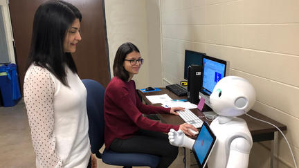 Dr. Arshia Kahn and Yumna Anwar with the robot Pepper