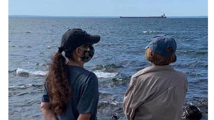 UMD Associate Professor Roxanne Gould and her mother making an offering of asema (tobacco) on the shores of Lake Superior.