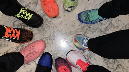 People putting their shoes in a circle on the floor.