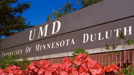 University of Minnesota Duluth sign with coral-colored geraniums.