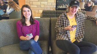 Corrin and Amanda sitting on a couch in Kirby Student Center on their cell phones