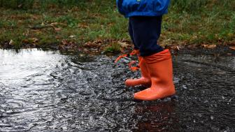 Person standing in puddle wearing red boots