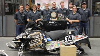 UMD's 2017 Clean Snowmobile Team standing by their snowmobile and trophies