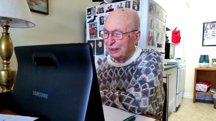 100-year-old Ralph Wheaton on a tablet participating in University for Seniors