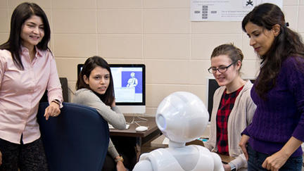 Dr. Arshia Khan with her students and robot Pepper.