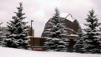 UMD's Weber Music Hall in the winter with snow-covered pines