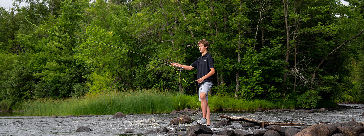 Freshman Robbie fly fishing at home