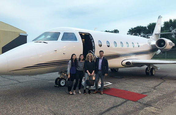 UMD student Maggie Zheng standing in front of a private jet with three coworkers