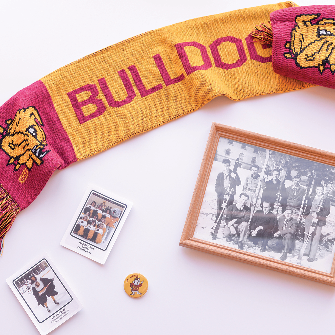 A Bulldog scarf, UMD mascot trading cards, pins, and ski team members photo.