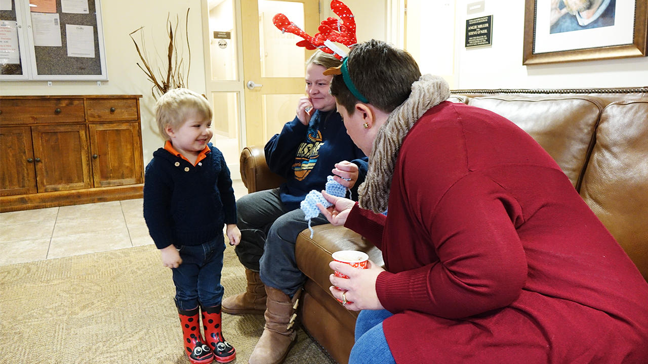 Young child looks at scarf with two adults at the Steve O'Neil Apartments in Duluth