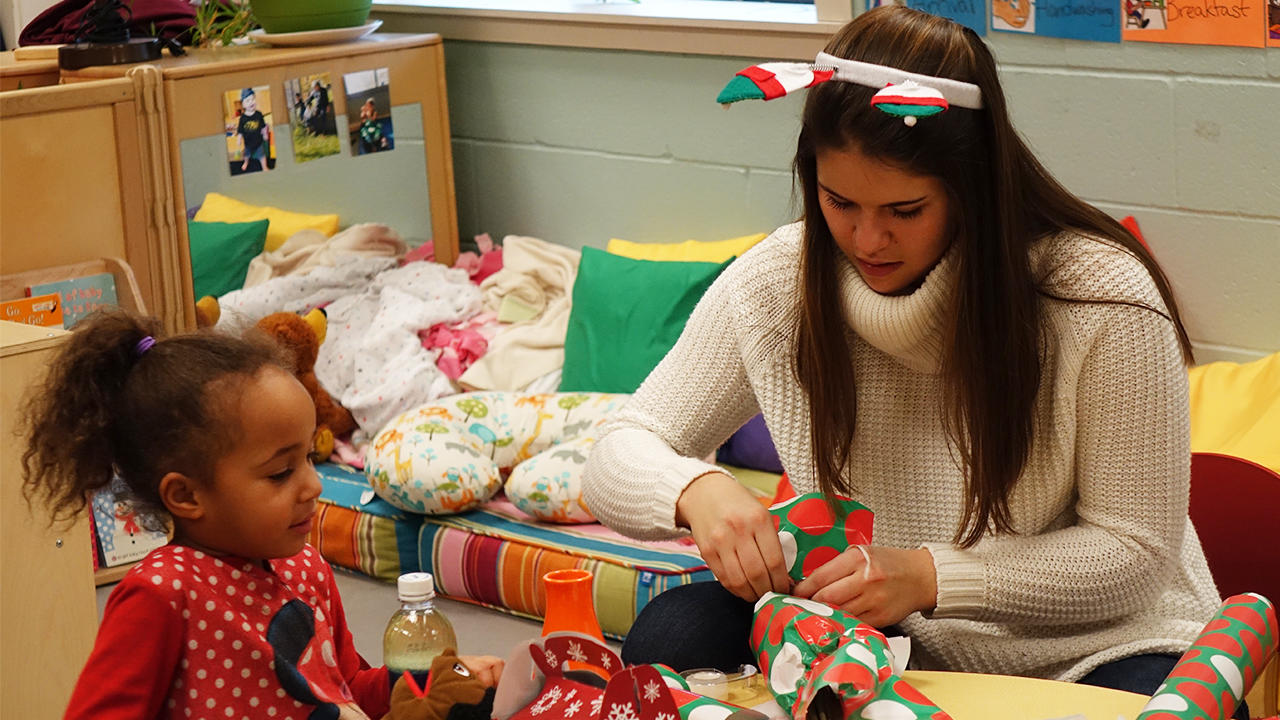 UMD student and a young child wrap a gift together
